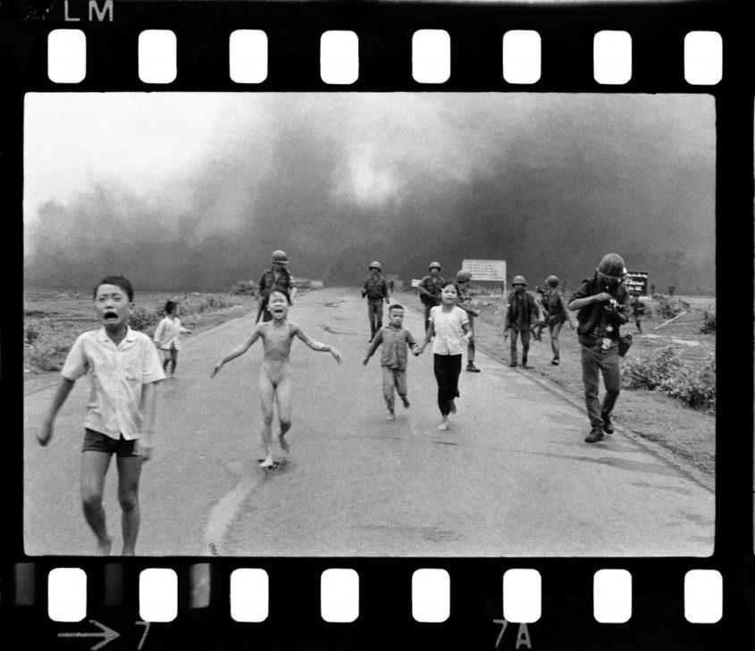 Kim Phúc (damals neun Jahre alt), läuft am 8. Juni 1972 nackt auf einer Straße in Trang Bang. Der Ort wurde von Vietnamesen mit Napalm bombardiert. Das Mädchen überlebte mit schweren Verbrennungen. Das Bild zeigt auch Kims älteren Bruder Phan Thanh Tam (12, ganz links), ihren jüngeren Bruder Phan Thanh Phuoc (5, links hinten) und Ho Van Bo und Ho Thi Ting, Cousin und Cousine von Kim, Mitte rechts. Ganz rechts ist der bekannte Fotoreporter David Burnett zu sehen, der gerade einen Film einlegt. Dieser Teil des Bildes wurde später abgeschnitten.